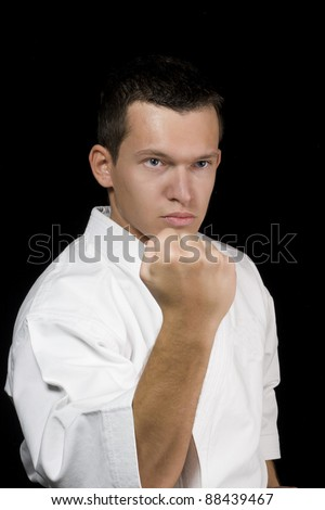 High Contrast karate young male fighter on black background. - stock photo