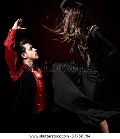 High contrast Young couple passion flamenco dancing on red light background. - stock photo
