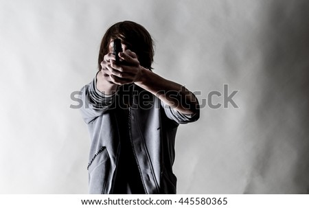 High contrasted shot is giving a dramatic result.Discolored  picture, of a teenager student  aiming with a gun. Focused in the foreground. - stock photo