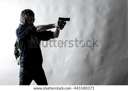 High contrasted shot is giving a dramatic result. Discolored  picture, of a teenager student having a backpack and aiming with a gun. - stock photo