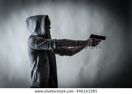 High contrasted shot to give a dramatic result. Discolored picture, of a teenager student wearing a hood and aiming with a gun.     - stock photo