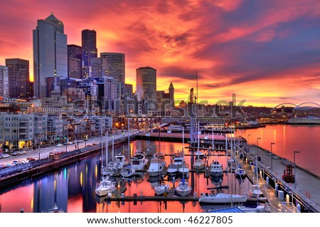High dynamic image of Seattle skyline in dramatic sunrise colors across pier-66 waterfront - stock photo