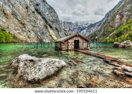 High dynamic range (HDR) image of boat dock hangar on Obersee mountain lake in Alps. Bavaria, Germany