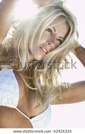 High Dynamic Range, HDR, photograph of a stunningly beautiful young blond woman in backlit by sunshine and wearing a white bikini