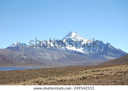 High elevation plain and lake under a looming snow capped mountain, Andes Mountains, Bolivia, South America