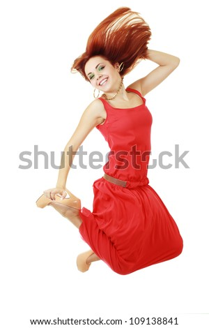 High-End Fashion Model with red hair red dress and heels jumping in studio on background - stock photo