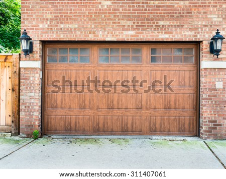 High end garage door on a brick house of a upscale neighbourhood - stock photo