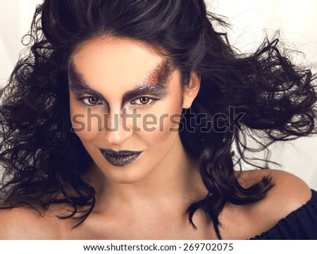 High fashion art look fantasy. Beauty portrait of glamour sexy smiling brunette young woman model with amazing sparkle black makeup, healthy curly blowing hair and fresh skin