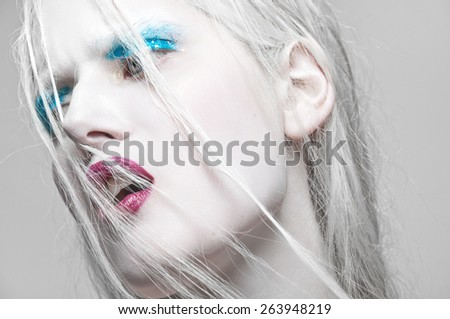 High Fashion Beauty Model Girl with blue Make up and Long Lushes. Red Lips. Dark Lipstick and White Skin. Vogue Style Portrait - stock photo