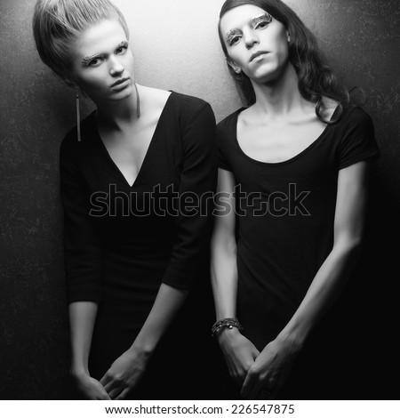 High fashion concept. Emotive portrait of beautiful blonde model and handsome long haired guy. Great arty makeup of silver foil. Perfect skin, hairstyle. Black trendy clothing. Studio shot