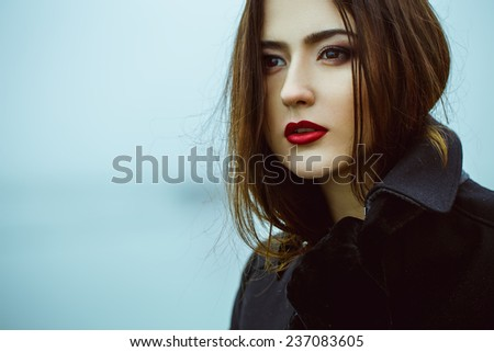 High fashion concept. Emotive portrait of beautiful brunette with long curly hair and perfect make up wearing black coat. Windy and misty weather. Italian luxurious style. Outdoor shot - stock photo