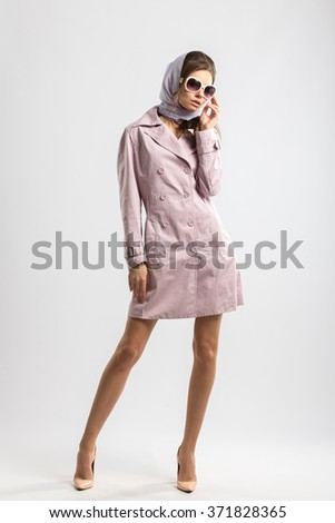 High fashion concept. Emotive portrait of beautiful girl with long hair and perfect make up, wearing pink coat. Italian luxurious style. Studio shot. Isolate.
