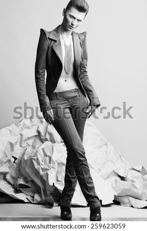 High fashion concept. Portrait of androgynous model with short hair wearing silver necklace posing over gray background. Pale skin, natural make-up. Luxury clothing. David Bowie style. Studio shot - stock photo