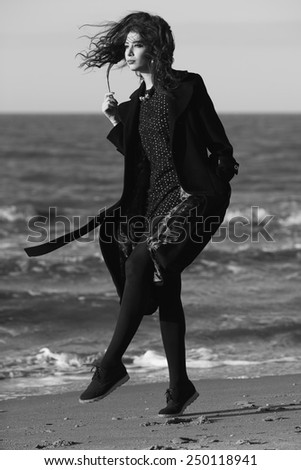 High fashion concept. Portrait of beautiful brunette with long curly hair wearing black coat and little black dress & feeling happy on the beach. Sunny weather. Italian luxurious style. Outdoor shot - stock photo