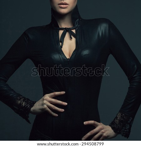High fashion concept. Portrait of beautiful young woman in black leather dress with lace posing over dark gray background. Perfect natural make-up. Healthy skin. Close up. Studio shot - stock photo