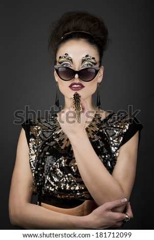 High fashion glamour model with gold dress & exotic make up