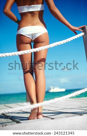 High fashion look. back of glamor sexy sunbathed model girl in white lingerie  behind blue beach ocean water on pier - stock photo