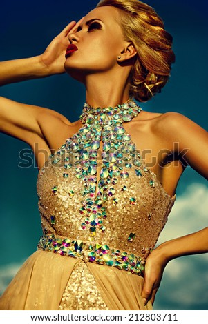 High fashion look.beautiful sexy stylish blond young woman model with bright makeup and red lips with perfect sunbathed clean skin with jewelery  in vogue style in evening dress behind blue sky - stock photo
