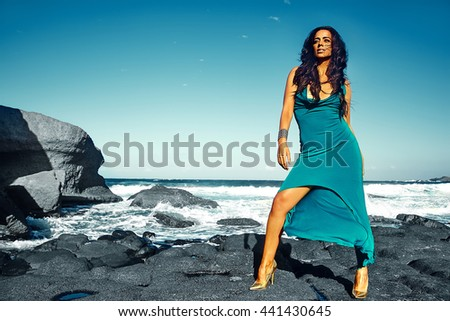 High fashion look. beautiful sexy stylish brunette smiling young woman model posing outdoors in vogue style in evening long blue dress behind sky and blue ocean - stock photo