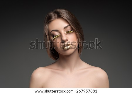 High fashion look, closeup beauty portrait of beautiful young woman model with bright makeup with perfect clean skin with colorful gold lips - stock photo