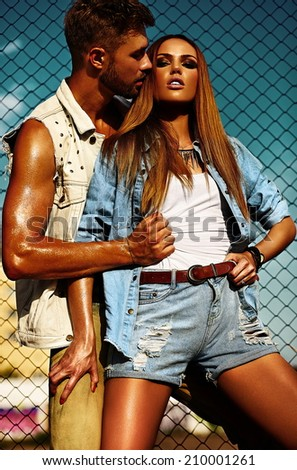 High fashion look.glamor beautiful couple sexy stylish blond young woman model with bright makeup with perfect sunbathed skin and handsome muscled man in vogue style in jeans outdoors behind blue sky - stock photo