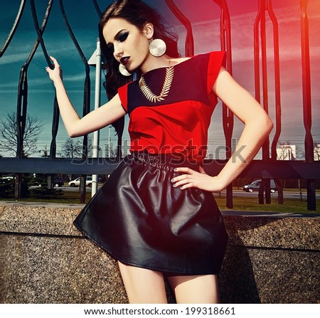 High fashion look.glamor beautiful sexy stylish brunette Caucasian young woman model in red colorful cloth with bright makeup outdoors in the street in vogue style - stock photo