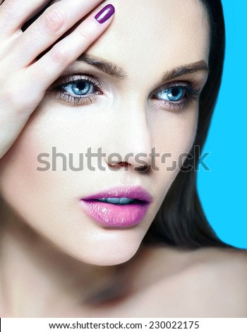High fashion look.glamor closeup beauty portrait of beautiful sensual  Caucasian young woman model with nude makeup   with perfect clean skin on blue background with pink lips and nails - stock photo