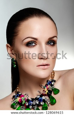 High fashion look.glamor closeup portrait of beautiful sexy brunette Caucasian young woman model with healthy hair,bright makeup,  with perfect clean skin with green accessory jewelery - stock photo