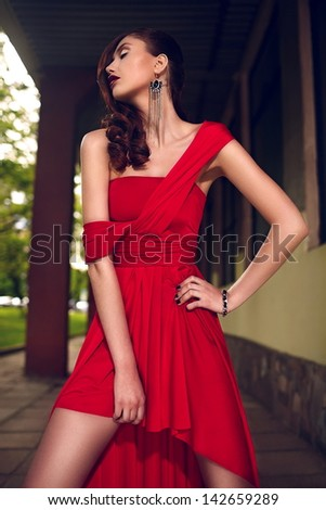 High fashion look.glamor closeup portrait of beautiful sexy stylish brunette Caucasian young woman model with bright makeup, with red dark lips, in bright summer red evening dress outdoors