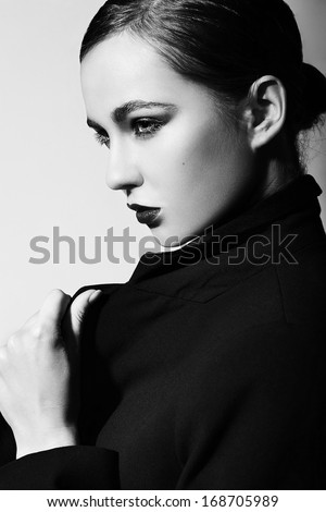 High fashion look.glamor closeup portrait of beautiful sexy stylish brunette Caucasian young woman model with bright makeup, with red lips,  with perfect clean skin in jacket in studio - stock photo