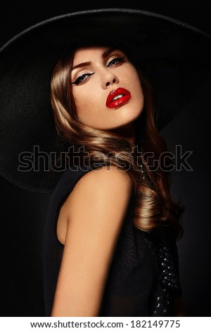 High fashion look.glamor closeup portrait of beautiful sexy stylish  Caucasian young woman model with bright makeup, with red lips,  with perfect clean skin in big black hat - stock photo