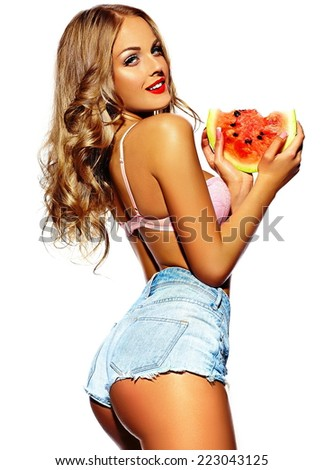 High fashion look.glamor closeup portrait of beautiful sexy stylish fresh blond young woman model with bright makeup, with red lips,  with perfect clean skin with watermelon in jeans - stock photo
