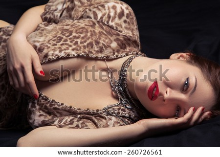 High fashion look. Glamor closeup portrait of beautiful sexy stylish woman model lying on black bed with bright makeup, with red lips, with perfect clean on bed - stock photo