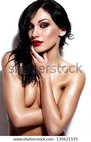 High fashion look.glamor portrait of beautiful sexy  Caucasian young brunette nude woman model with bright makeup with red lips on black background with perfect wet body - stock photo