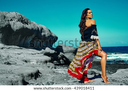 High fashion look.glamor sexy Caucasian model girl in red colorful black dress posing behind blue beach ocean water in vogue style - stock photo