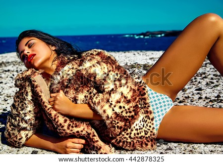 High fashion look.glamor sexy sunbathed Caucasian model girl in leopard fur coat posing behind blue beach ocean water in vogue style  - stock photo