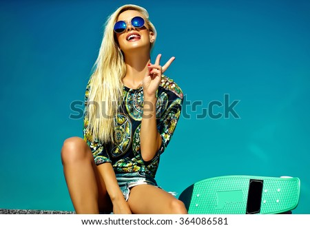 High fashion look.glamor stylish sexy beautiful young cute blond model girl in summer bright casual hipster clothes with skateboard behind blue sky showing victory sign
