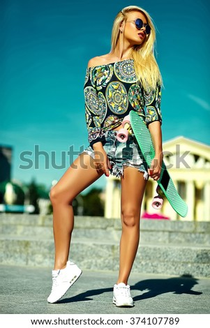 High fashion look.glamor stylish sexy beautiful young cute blond model girl in summer bright casual hipster clothes with skateboard posing behind blue sky  - stock photo
