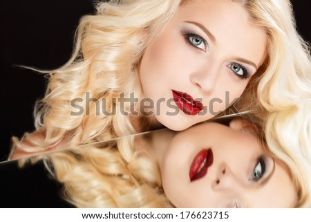 High fashion look.glamour fashion portrait of beautiful sexy blonde woman female model with bright makeup and red lips and her reflection in mirror table on dark with perfect skin - stock photo