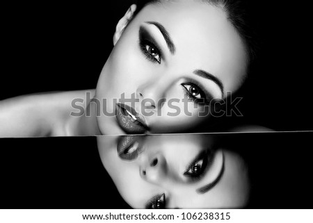 High fashion look.glamour fashion portrait of beautiful sexy brunette girl with bright makeup and her reflection in mirror table on dark - stock photo