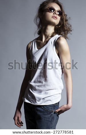 High fashion look. Portrait of a fashionable model with natural make up and perfect skin, dressed in men's jeans, white shirt and stylish round glasses.  Studio shot - stock photo