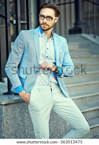 High fashion look.Young stylish confident handsome businessman model in suit clothes lifestyle in the street looking at his watches - stock photo