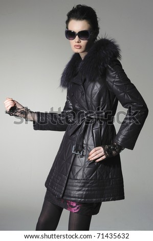 High fashion model in autumn/winter clothes wearing sunglasses posing - stock photo