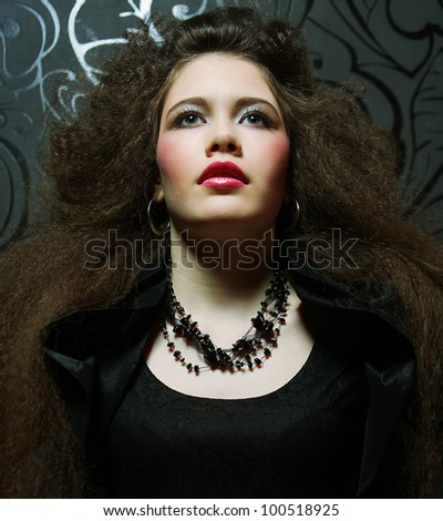 High fashion model in black dress, with creative hairstyling on black background - stock photo