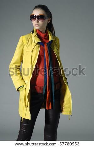 High fashion model in fashion dress wearing sunglasses posing in the studio - stock photo