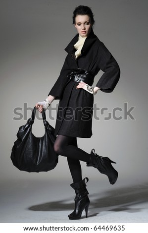 High fashion model in winter fur coat clothes with bag posing in the studio - stock photo
