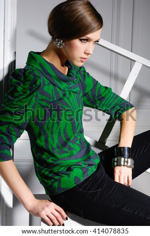 High fashion model sitting cube posing wooden ladder in the studio