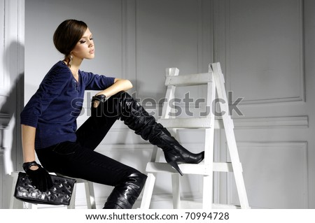 High fashion model sitting cube posing wooden ladder in the studio - stock photo