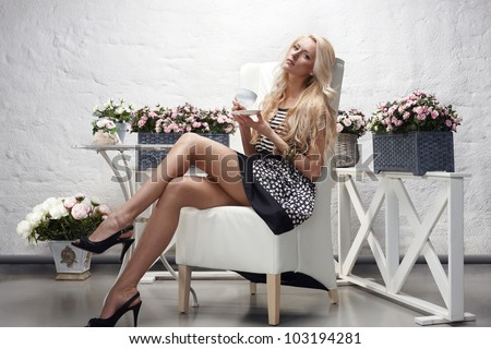 High fashion model sitting posing holding tea cup - stock photo