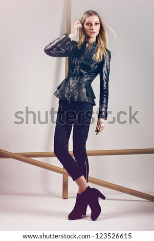 high fashion model wearing leather jacket, black trousers and black high heels posing in the studio - stock photo